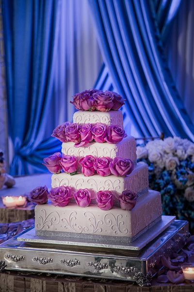 Glam purple and white wedding cake idea - four-tier white square-shaped wedding cake with purple roses and piped details on silver display {Joshua Zuckerman Photography}