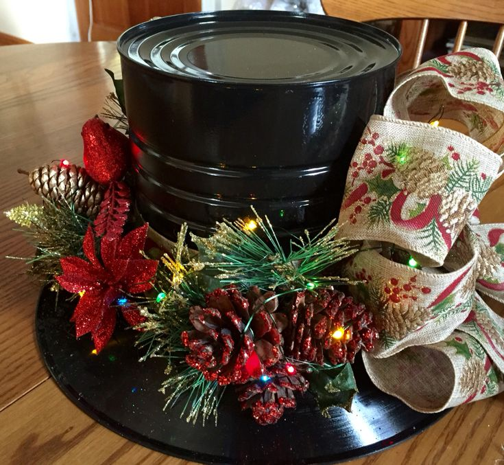 Top hat Centerpieces made from tin coffee can and a record with ribbon and holiday picks                                                                                                                                                                                 More