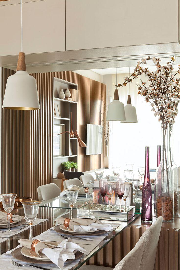 Decoração de apartamento pequeno e charmoso com ambientes integrados com ripas de madeira. Na sala de jantar mesa de jantar de vidro retangular, cadeira estofada, pendente e flores. Taça, taça roxa, anel de guardanapo de cobre.