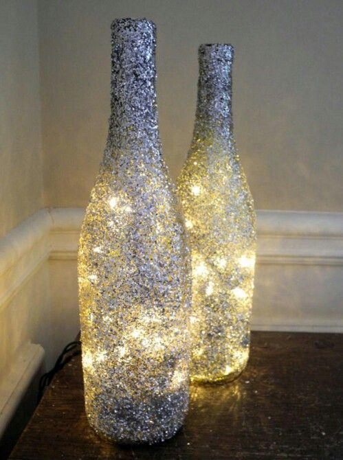 Flasker dækket med glimmer - og jeg synes det ligner at der ligger en lyskæde nede i - skønt og nem idé! Må på udkig efter små lyskæder - Flaskerne skulle jeg kunne få tømt herhjemme fra ;)