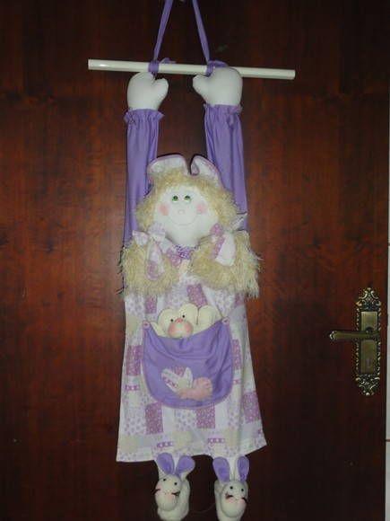 Boneca porta fraldas e/ou porta pijamas. Na parte de trás tem uma abertura para colocar o pijama ou fraldas ou o objeto que desejar. Ela fica pendurada na parede ou porta. Confeccionada em tecido 100% algodão.