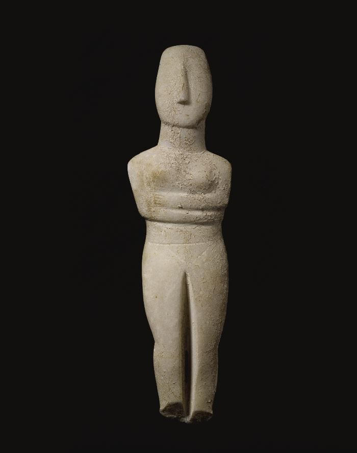 Cycladic marble figure of a goddess, attributed to the Rodgers Sculptor, Early Bronze Age II, circa 2500-2400 B.C. Lying with her arms folded beneath her breasts, with stout neck, lyre-shaped head, aquiline nose, and high straight forehead, the paint ghost of the left eye visible, 41.3 cm high. Private collection