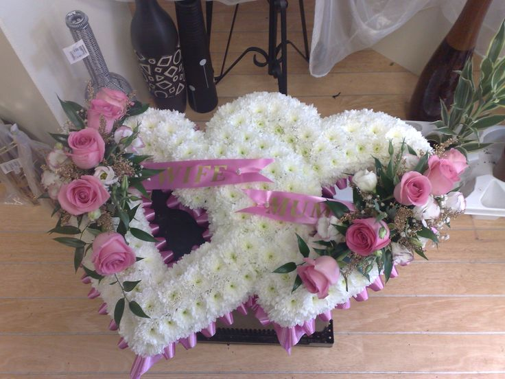 Double heart or joined hearts completed with roses, ribbon trim and sash.