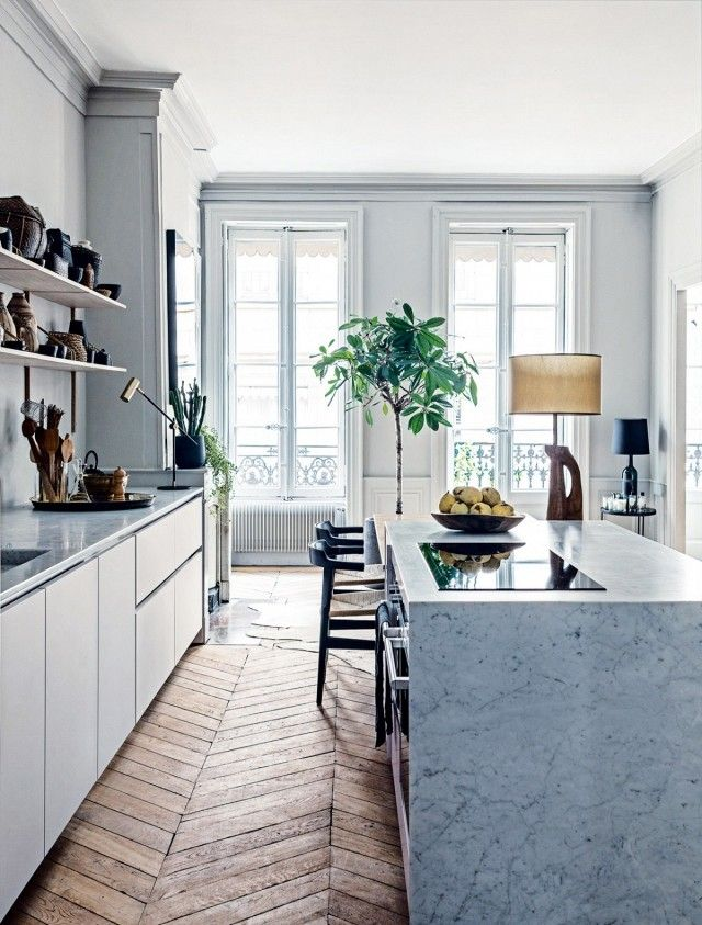 Modern kitchen with marble countertops, gray hues, and parquet floors