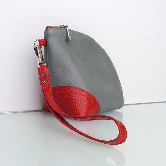 My bicolor / color block serie Q(uarter)-bag clutches This elegant bag is for any occasion.  You can use it as a evening clutch, a bag-organizer, or cosmetic bag. This clutch - is made light grey smooth cow leather and red lizard print embossed calfskin.  - has a red and silver metal zipper with a luxury metal zipper pull  - has a detachable wristlet strap.  - is lined with a striped cotton - has a small leather pocket inside.    The design makes the bag very spacious, yet compact. Do you…