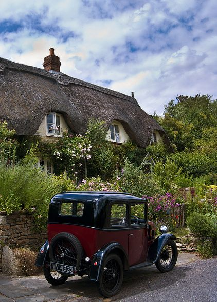 Thatched cottage and vintage car in Lacock, Wiltshire, England.  The village of Lacock is mostly owned by the National Trust.  The village has been used in films and movies due to its old world charm.