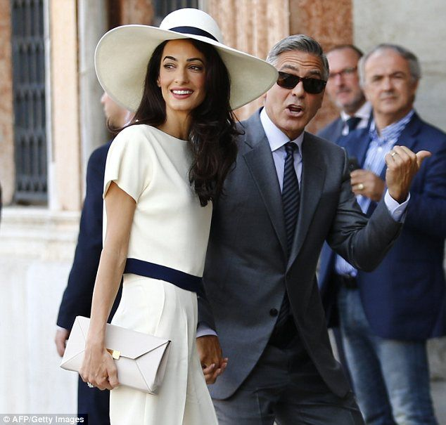 Glamorous: George Clooney displayed his wedding band while his glamorous new wife flashed ...
