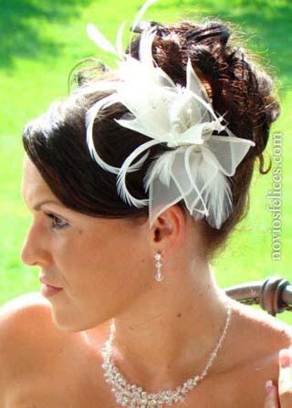Peinado de novia con moño alto de rizos y fascinante tocado de flores y finas plumas