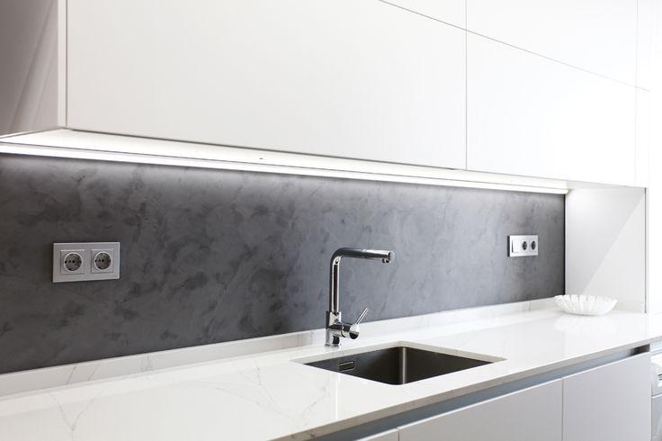Muebles de cocina blancos, pare en microcemento gris, encimera porcelanica. Fregadero bajo-encimera.