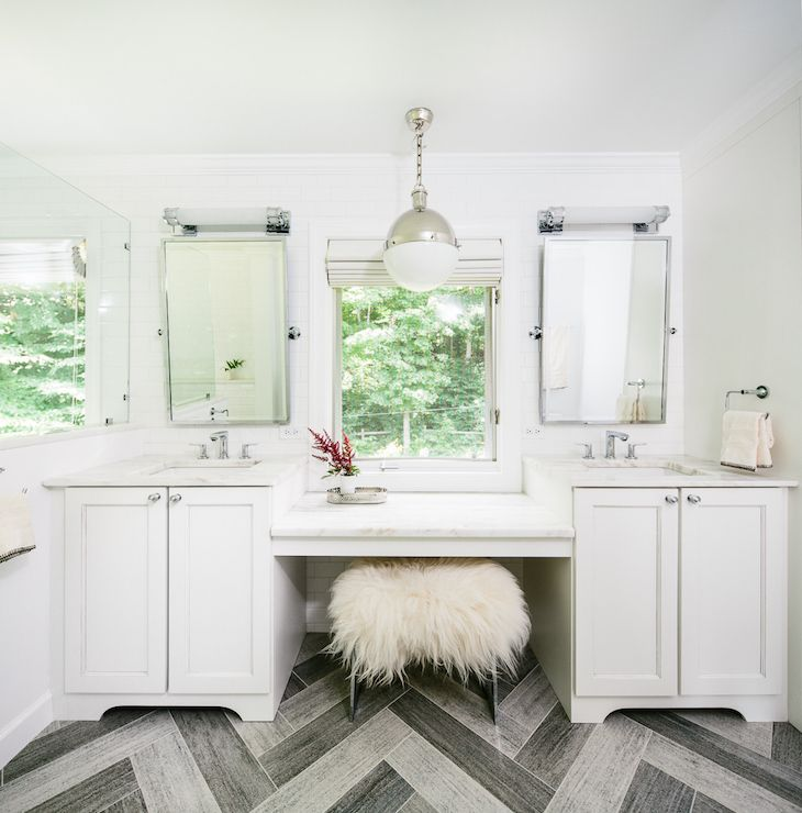 Fabulous master bathroom boasts separate his and her vanities fitted with white marble countertops framing square sinks and polished nickel faucets under matching rectangular pivot mirror illuminated by long sconces flanking drop-down make up vanity.