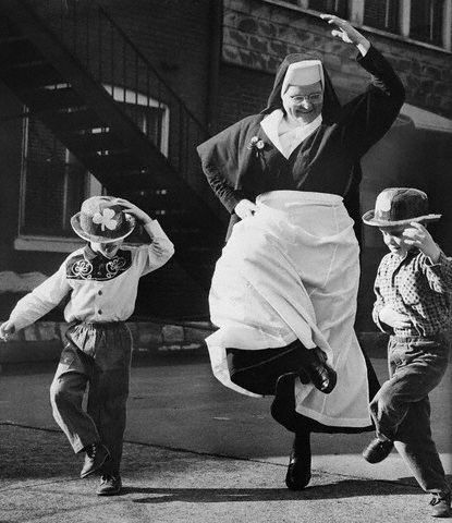 """""""In jig time for St. Patrick's day are Sister Mary Justus of the Sisters of the Sister of Notre Dame and two young friends, Charles Kelly (left) and Bobby Morris, who reel to the glory of Ireland's Patron Saint at St. Elizabeth's day nursery."""" 