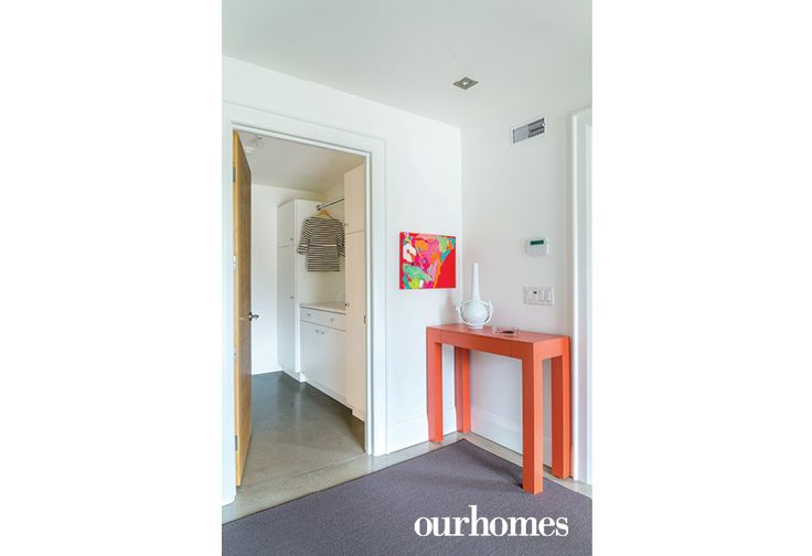 "A slim, orange laminate custom table designed by Sharp carries a bowl for keys inside the front entry. Through a door, the owners access the laundry room. Abstract canvas for this spot by Missy Sharp.     See more of this home in ""3 Hard-Working Mudrooms Share Tips and Tricks"" from OUR HOMES Southern Georgian Bay Ski Season 2017    http://www.ourhomes.ca/articles/build/article/3-hardworking-mudrooms-share-tips-and-tricks"