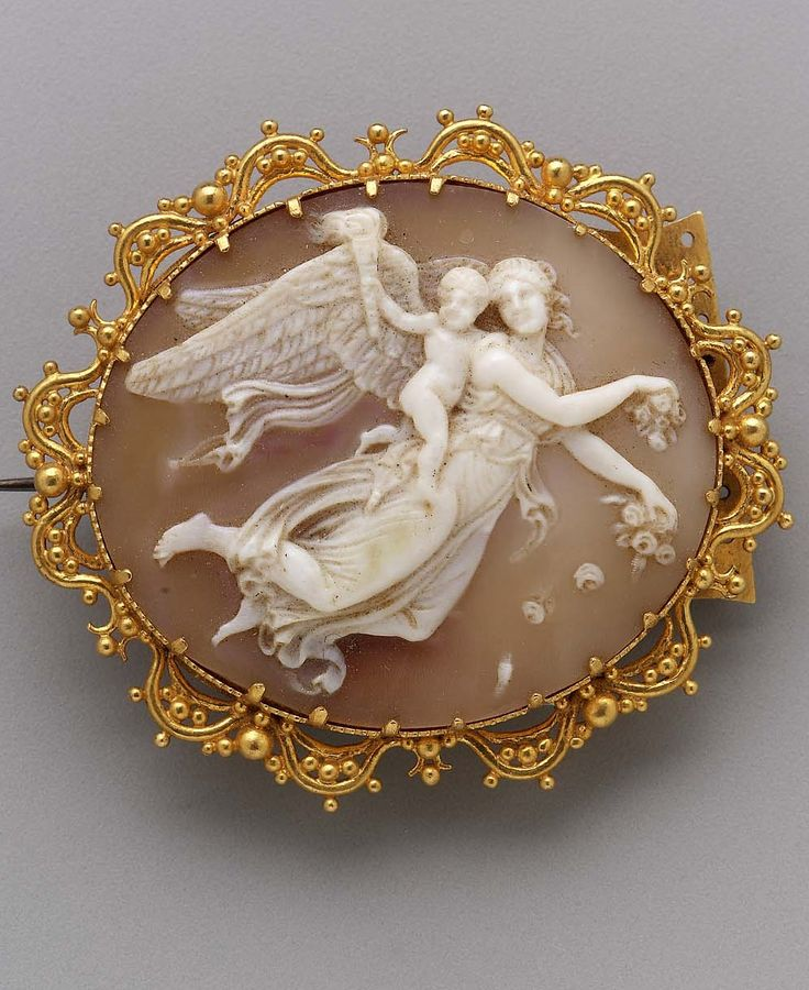 Brooch, Italian, mid-19th century. A large oval cameo prong set in gold in a bezel surrounded with an openwork wire and ball frame. The image shows a winged goddess strewing flowers with cupid on her back carrying a torch. This is a conflation of Venus with her cupid and Victory with the upright lit torch which was a Renaissance interpretation of Flora.