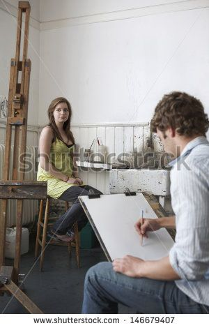 Male student sketching female model in art class
