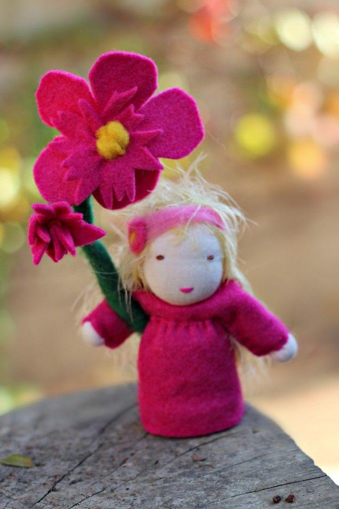 blurred orangey background. 121024 Jill Gallagher's pink flower fairy. Wednesday Morning Craft Group. Waldorf Spring Season Nature Table top doll. Handmade miniature fantasy doll. Photo by Jzin. Waldorf School of Orange County, Costa Mesa, California USA.  CastleofCostaMesa.Com