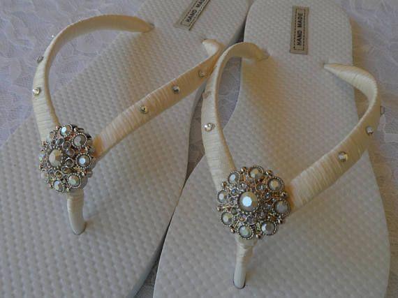 Mariée tongs sont un accessoire parfait pour vous mariage d'été... Ces flip flops sont enveloppés avec ruban de satin Ivoire dans les bretelles, sur le côté a Crystals de Swarovski et la façade est ornée de strass Ivoire magnifique. Je peux faire vos tongs dans vos couleurs de