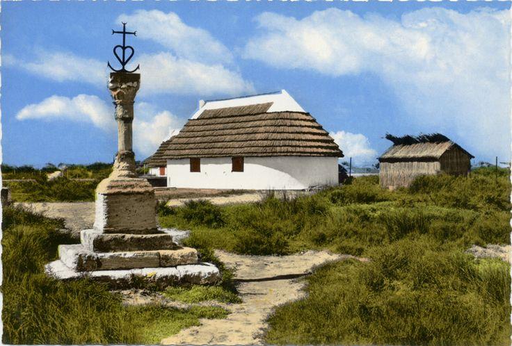Les cabanes du front de mer aux Saintes-Maries-de-la-Mer (Camargue) et la croix du gardian