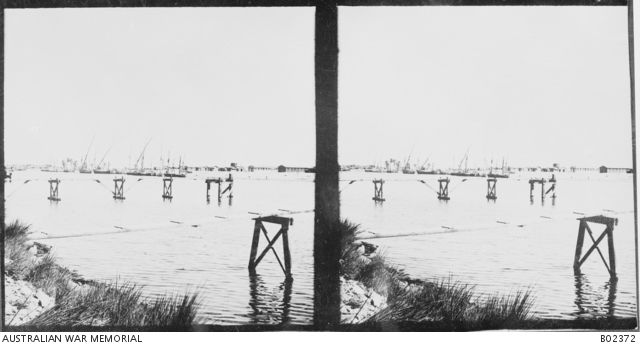 A view of Kantara on the Suez Canal, a large railway centre, which was the chief depot for the military stores and requirements of the Australian Light Horse.  In the foreground are two walkways leading to loading platforms in the canal. This is one half of a stereo image. Egypt: Suez Canal, Kantara c 1917