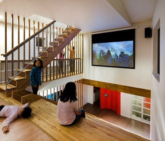 The Panorama House by Moon Hoon offers built-in home theater stadium seating (and a slide for kids and adults alike): The focal point of this Korean residence is the central multifunctional area, namely the wooden staircase which integrates a slide, bookshelves, reading nooks, and even cinema seating oriented towards a projection screen.