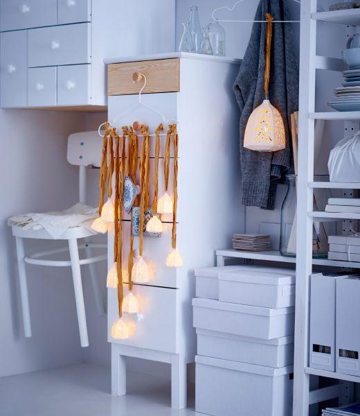 LED lampáše IKEA STRÅLA sú zavesené s rustikálnymi stuhami z vešiaka na šaty a tvoria sivatočnú svetelnú ozdobu.