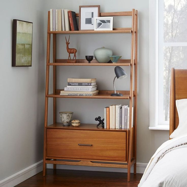 Library building. Inspired by American modern design, the Mid-Century Wide Bookshelf borrows its slim legs and bevelled edges from iconic '50s and '60s furniture silhouettes. Featuring three spacious fixed shelves and a filing cabinet drawer, it's a practical storage piece in the living room or study.