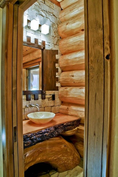 ery cool - rustic and logs... love the arched log under the sink... For my log cabin in Colorado someday... i like the big pieces of log, and the way the counter is made... Here the bathroom walls are outfitted with bare wooden logs, and the vanity is designed with tree bark and wood. Even the natural wood door paneling greets you into this rustic retreat.