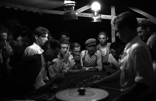 """David Seymour - Olympia. GREECE. 1951; """"At the full moon in September, the traditional time for ancient Olympic games, a panegyreis (county fair) takes place. The biggest attraction of the fairgrounds are the dozens of gambling tables, mostly roulette. A wooden disc with 37 sections was set in motion and the """"croupier"""" threw a dart into the disc. When the disc stopped spinning, the number was read and the winners were paid. People play till late at night, and much money is lost."""""""