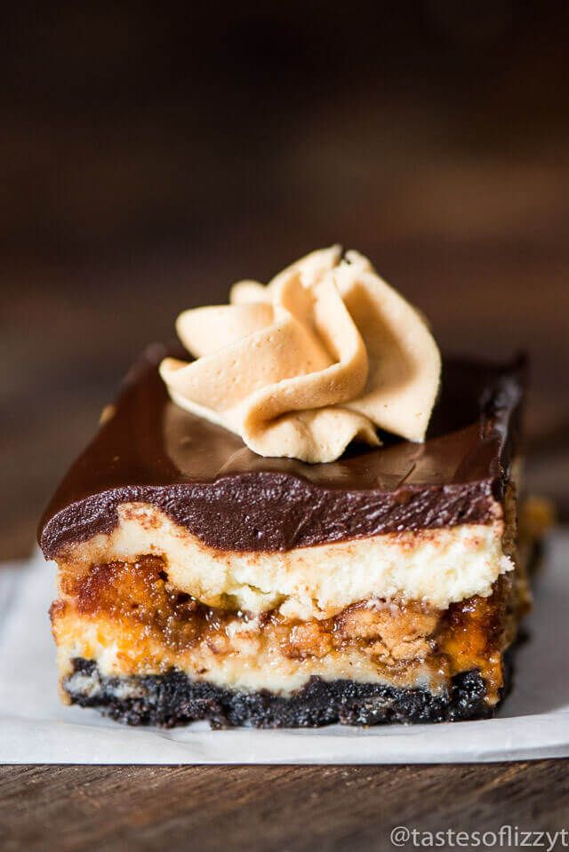 Reese's Butterfinger Cheesecake Bars are our copycat version of The Cheesecake Factory's Adam's Peanut Butter Cup Fudge Ripple Cheesecake. Creamy cheesecake stuffed with two kinds of candy bars, caramel, and topped with chocolate ganache and peanut butter frosting.