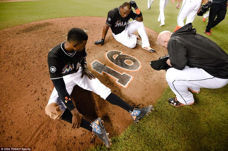 Miami Marlins second baseman Dee Gordon (left) center fielder Marcell Ozuna (top) and relief pitcher Mike Dunn (right) take a moment in honor of deceased Marlins starting pitcher Jose Fernandez at the pitchers mound