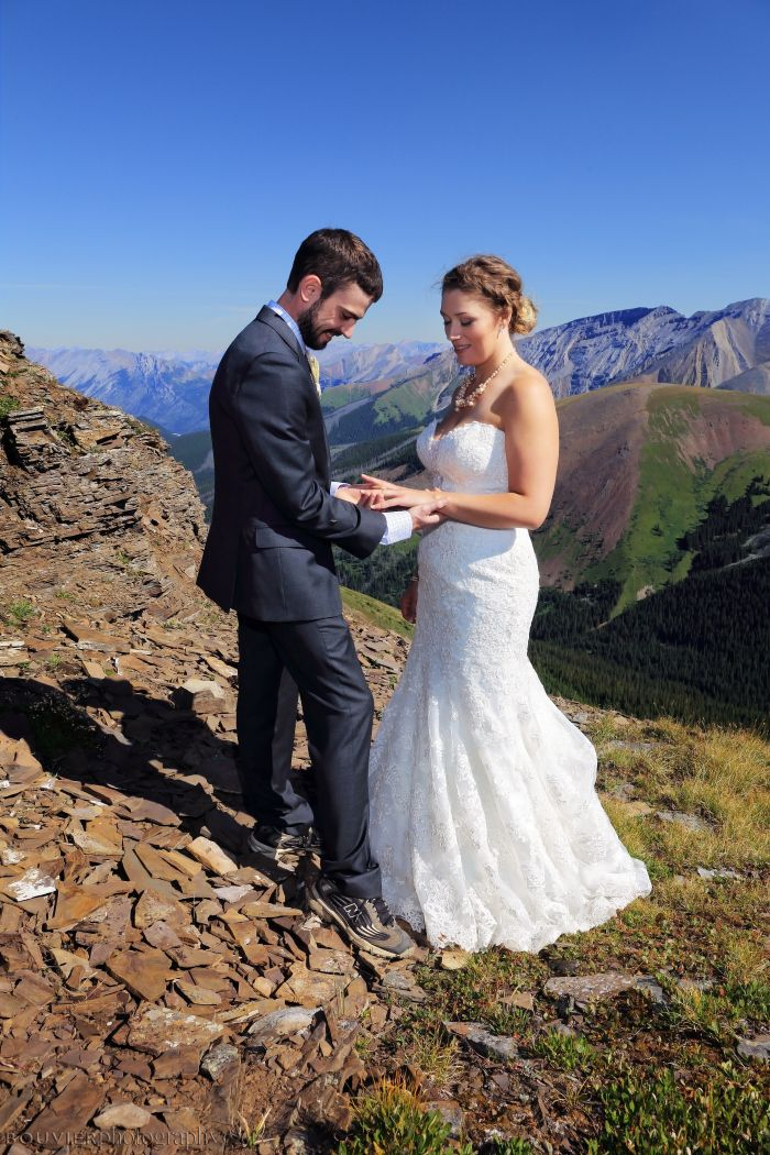 Groom placing ring on bride's finger in mountain top ceremony in Canmore, Alberta. Summer heli-wedding. Canmore Alberta wedding.