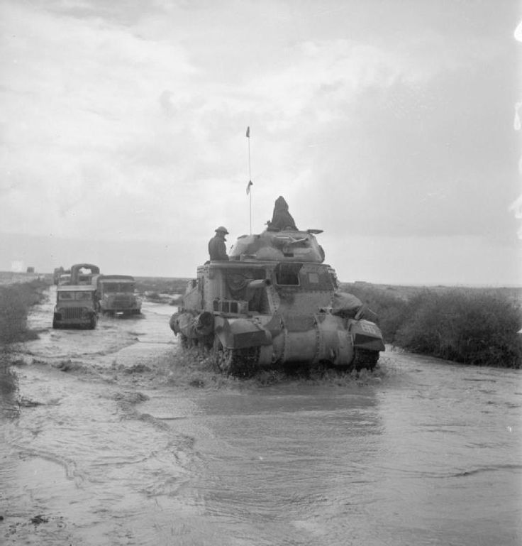 a grant tank and trucks make their way along a road flooded by recent rains while