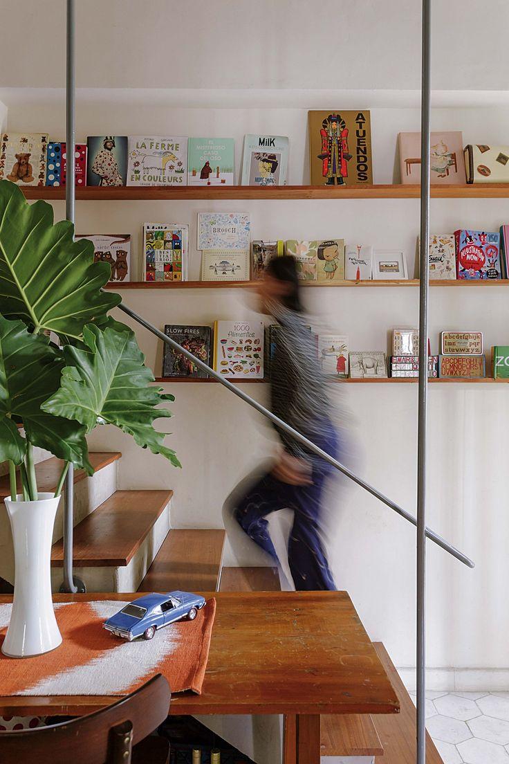 escalera de hormign y escalones de madera con estantes y libros que acompaan el recorrido