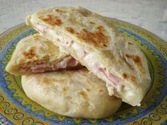 Pupusas A tésztához:      30 dkg liszt      1 tk sütőpor      1 kk só      0,5 dl olaj      1,5 dl víz   A töltelékhez:      12 dkg reszelt sajt      12 dkg sonka, apró kockákra vágva      3 ek tejföl