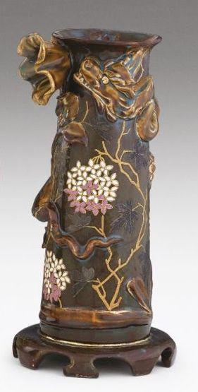 Zsolnay fedeles díszkorsó  Korongozott porcelánfajansz. Elefántcsontszín alapon kidomborodó, magastüzű, színes mázakkal festett és kontúraranyozott peóniák között kakasok és tyúk ábrázolása. Fülein virágdekor, nyakán és fedelén stilizált, indás díszítmény. masszába nyomott 563 (formaszám)  és máz alatt kékkel festett családi jegy.  Zsolnay, Pécs, 1882.  M.: 39,5 cm B17/k350