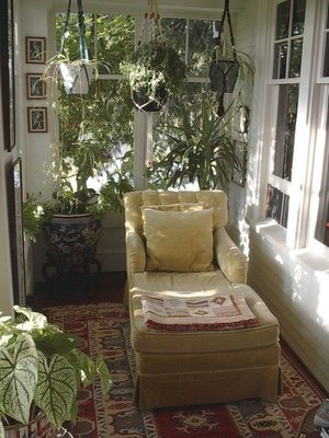 Enclosed front porch with plants, artwork, cozy rug, upholstered chaise lounging chair with pillow and throw....
