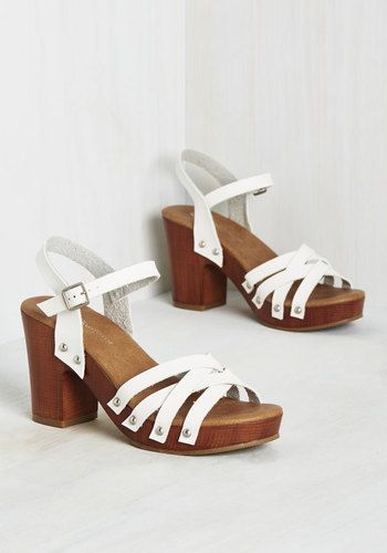 When the frost melts from the Stockholm forecast, you eagerly buckle into these white heels and hop on the metro downtown. The only thing more satisfying than the first outdoor fika is savoring it in the silver grommets and faux-wood platforms of these strappy sandals. Life couldn't be 'Swede-r'!