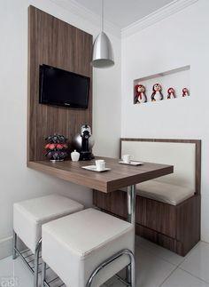 Praticidade: A bancada de madeira dá suporte para a TV, serve de mesa de jantar e ainda reserva o cantinho do café. O banco em estilo jogo americano traz o ar das cafeterias à sua casa!
