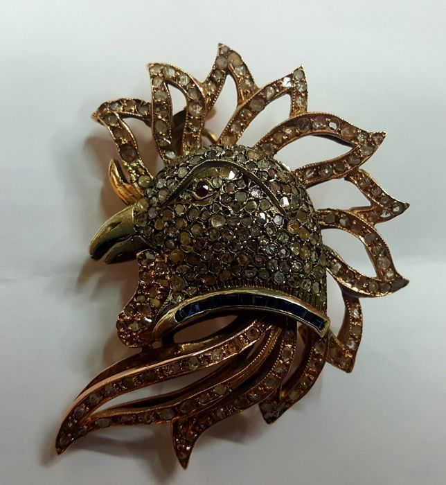 Online veilinghuis Catawiki: Haanvormige broche in roodgoud met diamanten, saffieren en een robijn.
