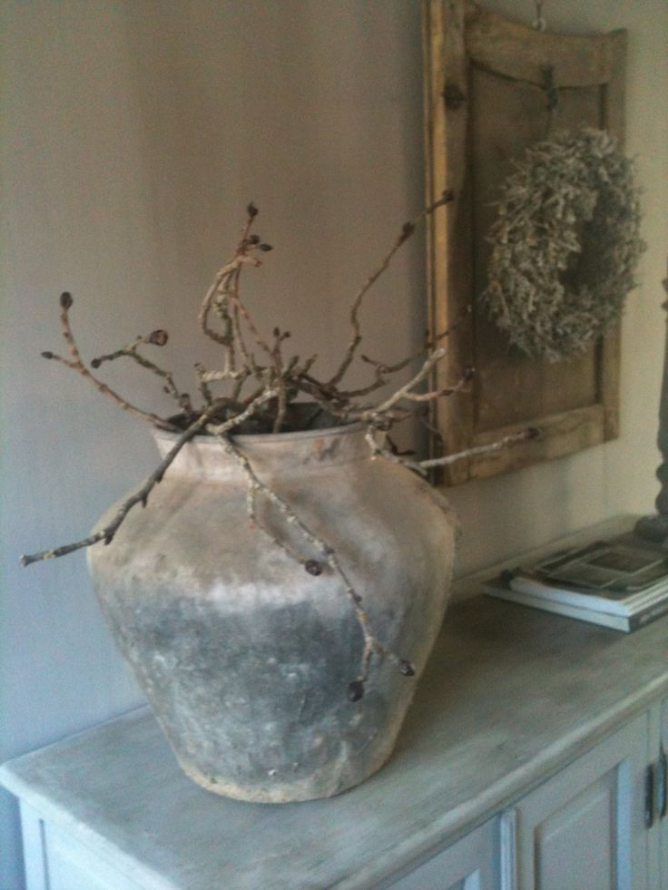 Twigs in a huge pot, framed dried wreath on the wall, antique buffet.
