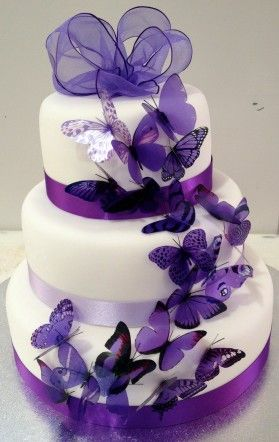 Wedding cake with purple butterflies and satin ribbon detail.