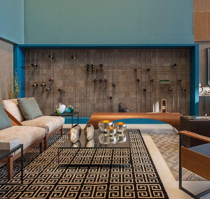 Liliane Bigaram e Bruna Fernanda desenharam uma adega executada com vergalhões e marcenaria, emoldurada na cor azul. A disposição das garrafas pode variar sempre. Para quem não tem uma parede com dimensões tão generosas, pode aplicar a ideia em uma área menor da sala.