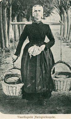 Een Vlaardingse haringverkoopster loopt over een laan. Op haar schouders rust een juk met eraan twee manden met in elk een haringtonnetje. In haar hand houdt ze een bord met erop twee haringen. Ze is gekleed in de Vlaardingse klederdracht. Prentbriefkaart. ca 1900 kaart C. Verboom #ZuidHolland #Vlaardingen