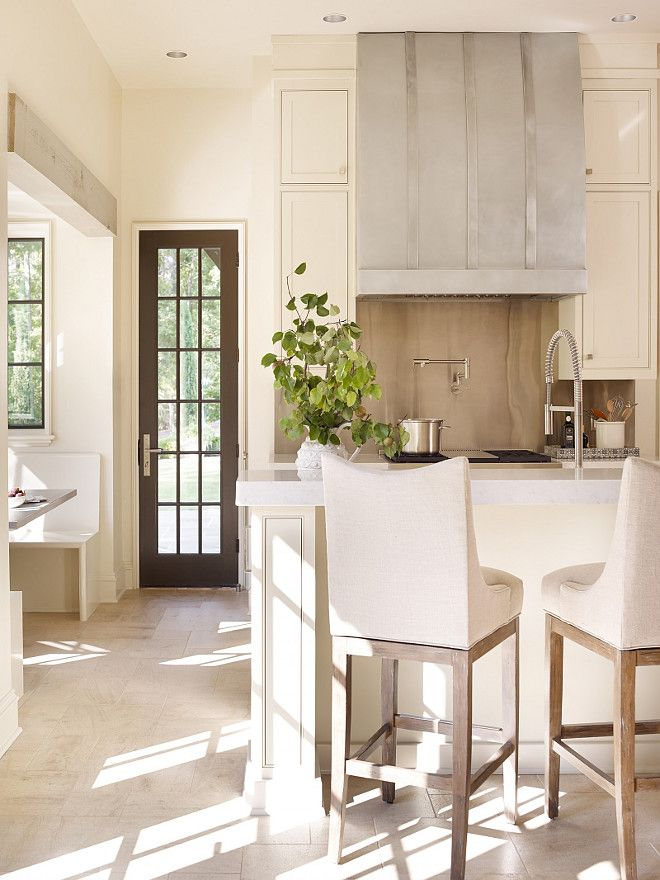 Neutral kitchen with ivory cabinet.Jeffrey Dungan Architects. Kitchen with banquette.Jeffrey Dungan Architects.  Kitchen with dark hardwood floors.David Small Designs.  Dalia Canora Design. The island countertop is a Super White Quartzite and the ...