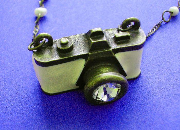 Een zeldzame 'Art Deco' hanger sautoir uit de jaren 30 beeltenis van een oude camera (Leica?)  Praat over zeldzame en ongewone! Mijn vrouw fould deze unieke tegenhanger enkele jaren geledenbij een vastgoed te koop. Ze vond het heel grappig en kocht het. Ze heeft verzameld Deco sieradenSinds 1989 en zag nooit zoiets. Het gemaakt van brons & koper geëmailleerd in een crèmekleur en de lens is ingesteld met een groot kristal. De keten heeft 4 geïnterlinieerde barok Seed Pearls2 aan iedere kant…