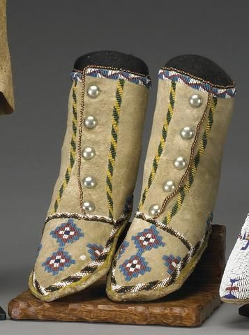 A pair of Apache beaded youth hightop moccasins.  Of softly tanned hide and thick stiff soles, stepped diamond motifs on the toes, striped beading elsewhere, German silver buttons for closure. length 9in, height 7in