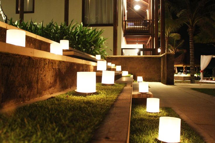Candles wrapped in fiber spread around villa area for wedding dinner party.