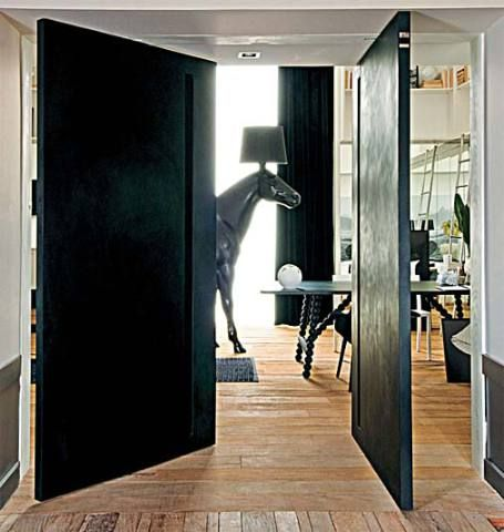 Portas com pivôs centrais fecham o espaço assinado pelo designer de interiores Francisco Cálio. As duas folhas (1,20 x 2,35 m cada uma) de MDF revestido com lâminas de Corian (DuPont) preto (6 e 12 mm, execução Studio Vitty) têm cavas no lugar dos puxadores.*