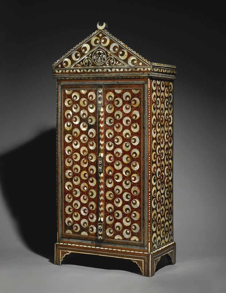 An Ottoman tortoiseshell, mother-of-pearl and ivory-inlaid cabinet with cintamani design, Turkey, 17th century of rectangular form on bracket feet with hinged, lockable double doors opening to reveal a bone and ivory diamond lattice design and three shelves, surmounted by a decorative arched pediment set with crescent moon finial, inlaid throughout with ebony, ivory, bone, tortoiseshell and mother-of-pearl, the dominating design centred on the cintamani motif, one side intentionally left ...