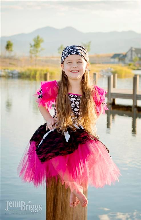 Adorable hot pink and black pirate tutu costume. This is a custom made all in one leotard style tutu dress. The top is made of a fully front lined 4 way stretch skull lycra with hot pink lycra trim and hot pink chiffon sleeves. The tutu is a 3 layer hot pink tutu with a lace overlay