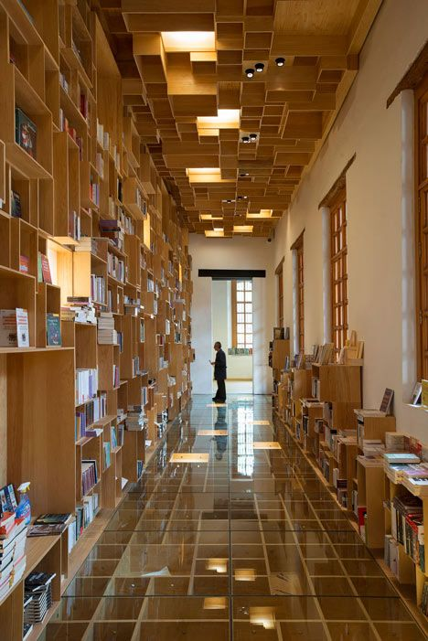 Mexican firm Taller 6A has renovated a library inside an eighteenth-century building in Mexico City, adding a bookshop with hundreds of wooden boxes on its walls, its ceilings, and under its glass floor.